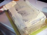 Prekrivanje (višje od načrtovane) torte z masleno kremo.