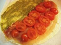 Tortiljo obloži s pestom, pršutom in češnjevimi paradižniki.