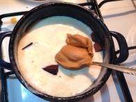 Nakoščkano čokolado prelij z vročo sladko smetano. Dodaj žlico arašidovega masla.