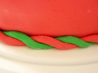 Iz ostankov roza in zelenega fondanta sem zvila dve kači, ju prepletla in tako kitko ovila okoli torte.